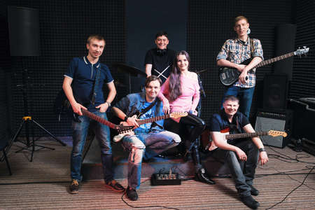 vocalist: Group photo of student music band. Smiling at camera male musicians and woman vocalist. Music band members posing on stage with their musical instruments.