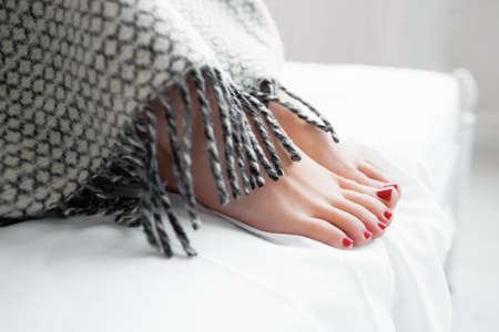 footcare: Female reams under warm gray blanket. Beautiful womans feet covered with gray blanket on bed. Close-up of covered female feet with red pedicure