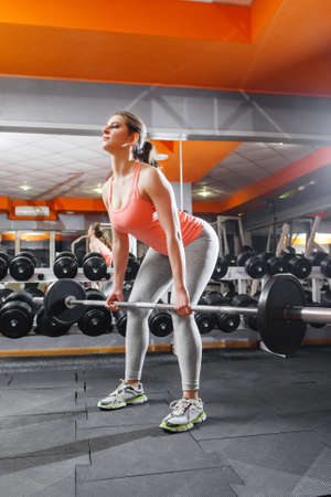girl squatting: Female athlete intensive training with barbell. Professional female sportsman doing strenth exersices at gym with barbell. Squatting with barbell girl Stock Photo