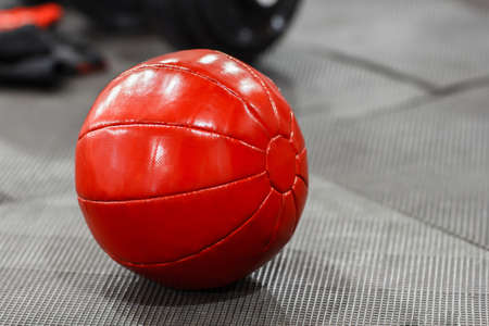 weighted: Red medicine weight ball on gym floor closeup. Weighted ball for doing fitness lying on the floor. Front view on red medicine ball in gym interior Stock Photo