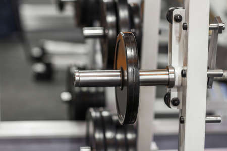 training device: Weightlifting training device at gym close-up. Exercise mashine with barbell. Weight plate on barbell at gym