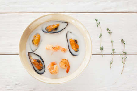 void: Bowl of seafood cream-soup with rosemary flat lay. Top view on bowl with white cream-soup with mussels and shrimps on white wooden background, decorated with rosemary, void. Creative food decoration Stock Photo