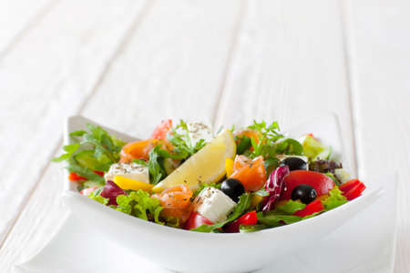 Fresh vegetable salad with salmon in white bowl copyspace. Front view on white ceramic bowl with tasty salad with salmon, brie, olives and slice of lemon on white wooden background. Free space Stock Photo