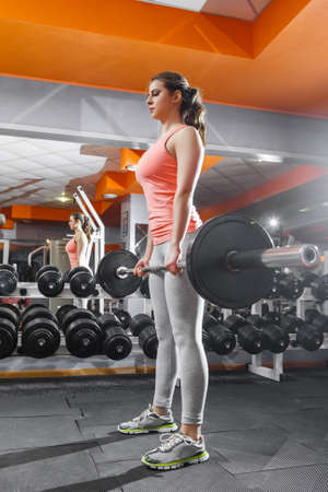 mirror on the wall: Sportswoman lifting hard barbell at gym interior. Young pretty bodybuilder woman in sportsuit doing workout with bar at gym against the mirror wall Stock Photo