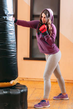 punching bag: Kicking punching bag kickboxing female athlete. Training at gym of beautiful female kickboxer with punching bag. Self defence training at gym by pretty woman in purple sport wear Stock Photo