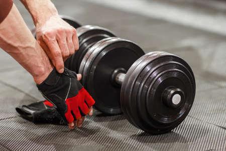 男をダンベルを曲げる前にスポーツ手袋をつけます。オスの運動選手は、ジムでバーベルの準備します。重量挙げトレーニングの準備