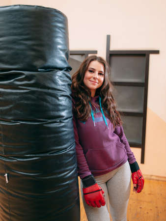 punching bag: Smiling athletic girl standing near punching bag. Pretty female kickboxer in red boxing gloves relying on punching bag at gym. Looking at photographer cute female kickboxer Stock Photo