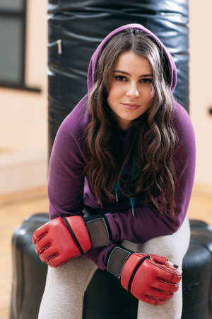 Young girl in sport wear, sitting on punching bag in gym . Pretty female athlete in red boxing gloves having rest on punching bag foundation.
