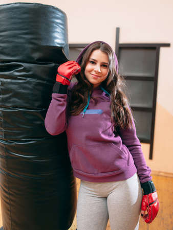 punching bag: Young female kickboxer posing near punching bag in gym. Photo of smiling pretty female athlete in purple sport wear and red boxing gloves, standing near punching bag at gym.