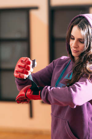 put on: Smiling female athlete put on boxing gloves at gym. Pretty girl in purple sporsuit put on red boxing gloves before active workout. Women self defence concept