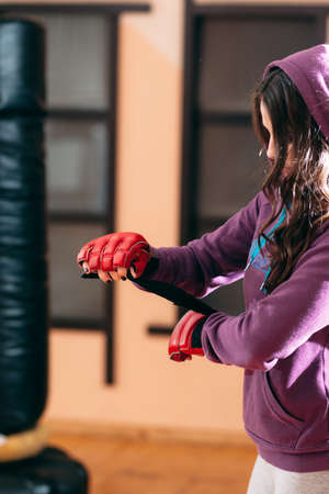 punching bag: Young sportswoman wrapping hands near punching bag. Sporty girl in sport wear at gym wrapping her hands with red boxing wraps. Ready for exercises or training with punching bag female kickboxer