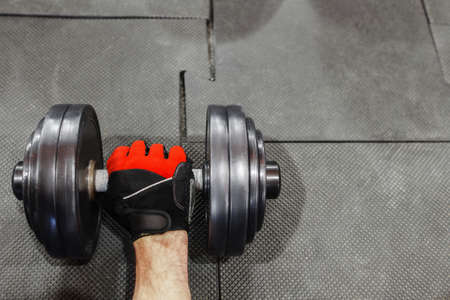 weightlifting gloves: Male hand in sport glove holding dumbbell void. Top voew on dumbbell on gym floor with athlete hand taking it. Professional athlete hand in gloves with dumbbell, copyspace