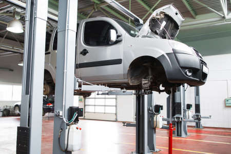 auto hoist: Car undergoing service in garage raised on lift. Front view on gray car without wheels raised on lift in garage with open hood. Auto service industry concept Stock Photo
