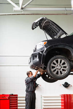 car hoist: Mechanic working under raised car in service station. Mechanic disassemble lifted on hoist car. Young male mechanic repairing SUV car in garage