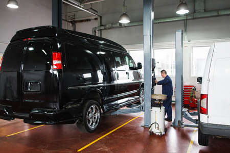 diagnosing: Mechanic rising car on lift before repairing. Male mechanic control black minibus rising on lift at service station. Black minibus lifting up for diagnosing or service maintenance by mechanic. Stock Photo