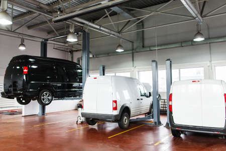 service lift: SUV big service station, black minibus raised up on lift. Front view on line of three cars in garage on service maintenance, two white pickups stay in stables, black minibus lifted up