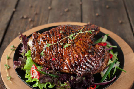 Grilled turkey thigh with lettuce and herbs on catering platter on blurred wooden table, copyspace. American thanksgiving traditional meal Reklamní fotografie - 60028722