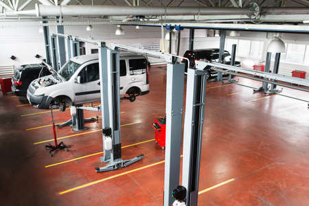 auto hoist: Garage with cars on service or repairing. Top view on professional service station , some cars on service maintenance, one car lifted up on hoist. Some free space