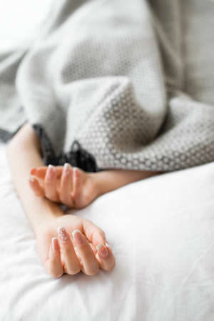 introvert: Sleeping introvert hidden from all the people under the blanket. Completely covered with gray blanket woman in bed, with her hands out of blanket. Focus on beautiful female hands with french manicure Stock Photo
