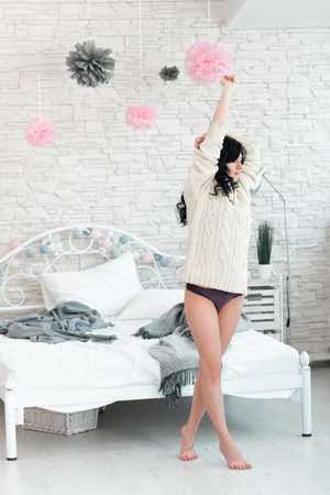 awaking: Hardly awaking woman in white pullover. Young brunette in white pullover and panties early in morning in her bedroom with raised hands barefoot on tiptoe