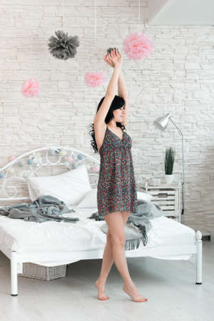 awaking: Young brunette female doing morning exercises in bedroom. Beautiful woman stretching near bed to awake. Full length image of slim young awaking woman