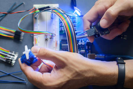 microprocessor: Robotics development closeup., electronic invention. Engineer, programmer, inventor hands with special cables, wires, working with breadboard and constructing robot at home. Modern technologies. Hobby