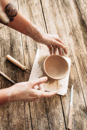 wood molding: Pottery and artisan hands on wood, potter workplace. Clay bowl molding at studio