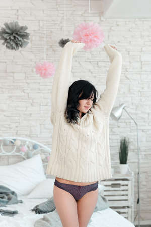 Sleepy woman in bedroom early in morning. Stretching woman near bed, just awaking. Drowsy brunette in white sweater and panties