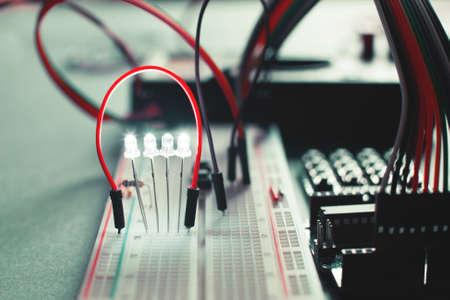 Close-up op elektronische raad in hardwarereparatiewerkplaats. Broodplank met speciale kabels en led. Elektronica diy ontwikkeling