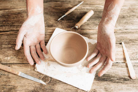 newcomer: Craftsman hands with pottery and tools on wood close-up. Newcomer at potter studio, workplace of sculptor
