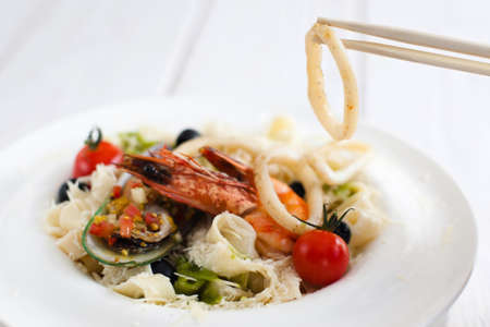 ingestion: Seafood eating with chopsticks, closeup. Squid ring taking with asian cutlery from plate with seafood mix meal Stock Photo