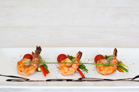 Grilled shrimps line on white plate on light wooden background, flat lay, copyspace for commercials, horizontal position