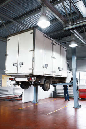 Truck on service in garage, lifted lorry diagnostics at workshop. Long-distance cars inspection before road.