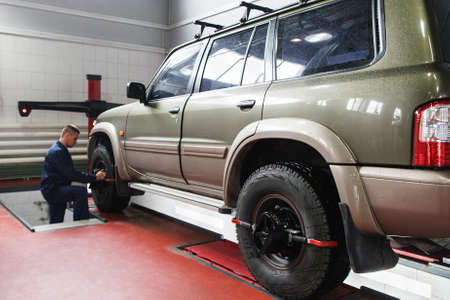 aligning: Wheel alignment for SUV in professional workshop. Modern auto service with high-level maintenance