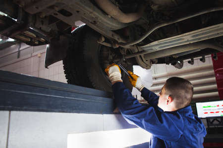 recovering: Mechanic recovering car suspension system at auto service. Garage worker restore the car in workshop