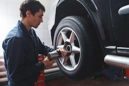정비사 자동 수리 가게에서 자동차 바퀴를 변경합니다. 차고에서 자동차의 비버 근처 작업하는 도구와 군인의 근접 촬영.