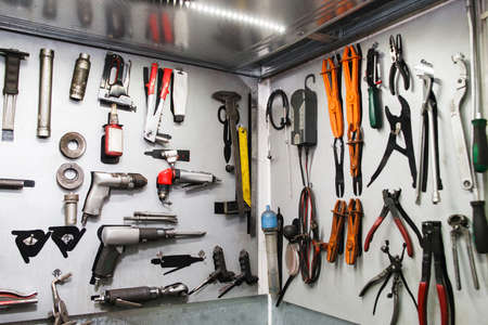 Assorted instruments for car maintenance on wall at service. Special tools for professional vehicle repairing Stock Photo