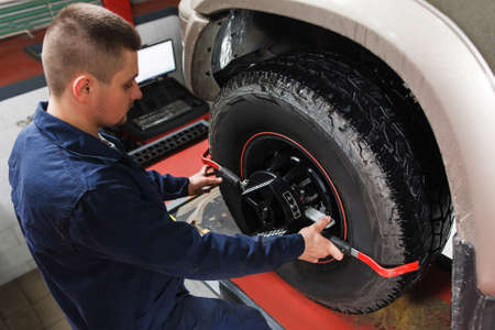 aligning: Mechanic tuning aligner for wheel alignment in garage closeup. Professional car maintenance in modern workshop