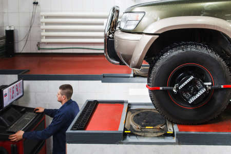 aligning: Computer diagnostics of wheel alignment for SUV at service. Professional car maintenance, modern technologies