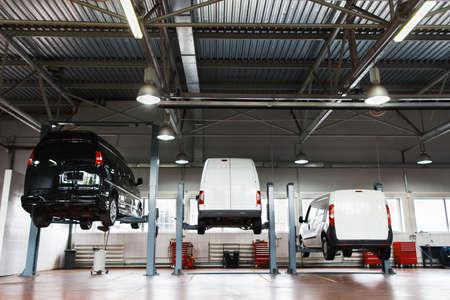 Inter de estación de reparación de automóviles, coches en el mantenimiento levantado en ascensores