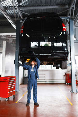 disassembly: Mechanic working with car suspension system. Automobile on maintenance at service