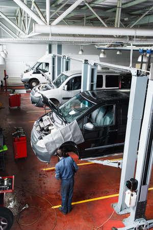 Car repair shop usual working day, auto service interior. Top view on  garage with