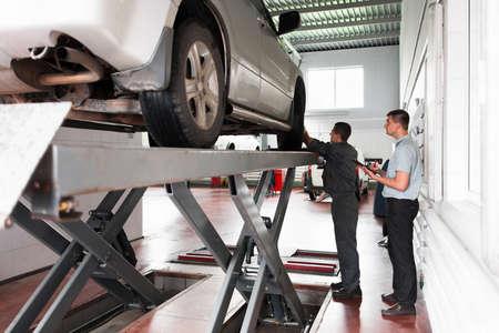 ispezione sistema di sospensione auto al workshop. diagnostica professionali di automobili, sollevati in ascensore in servizio moderno, l'esame garanzia auto
