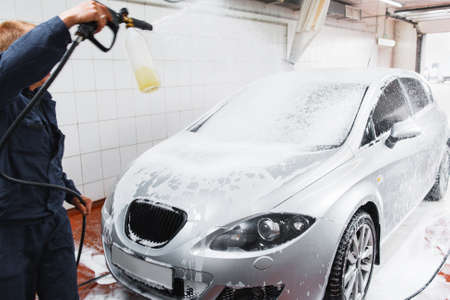 serviceman: Serviceman in carwash washing car with hose. Handle automobile cleaning at special store, complex service