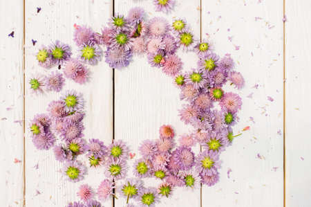 circlet: Circlet frame of purple flowers on white wooden background. Stock Photo