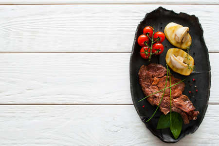 Grilled steak and potato on white wooden background, flat lay, copyspace. Top view on clean table with black plate, served with steak and vegetables, restaurant menu photo