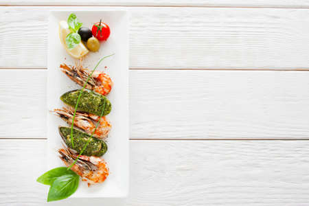 free dish: Plate with prepared seafood on white wooden background, copy space. Vertical position of dish with stuffed mussel and grilled shrimp, menu photo, free space for text