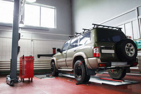 aligning: SUV wheel alignment at professional service. Car ready for maintenance in modern garage
