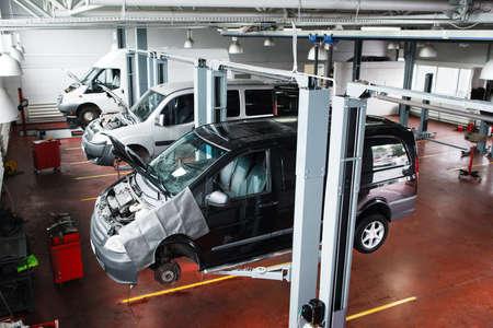 sollevamento auto industriale a moderno negozio di riparazione. I minibus servizio di manutenzione in officina professionale.