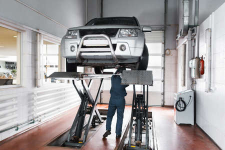 disassembly: Mechanic inspecting car suspension system of lifted automobile at repair service station. SUV service maintenance at modern garage